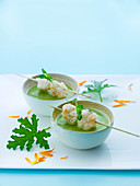 Herb soup with scampi kebabs