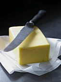 A pat of butter on parchment paper with a knife