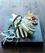 White asparagus and a peeler on a wooden board