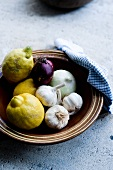Lemons, garlic and onions in a clay dish