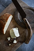 Goat's cheese and a knife on a wooden board