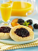 English muffins with plum and blackberry jelly and orange juice