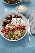 A Greek appetizer platter with olives, pepper and feta cheese
