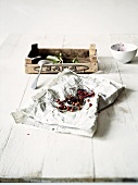 Cherry stones on newspaper in front of a wooden crate