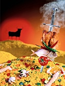 A fish and a chicken skewered onto a sword and stuck in a mountain of paella (Spain)