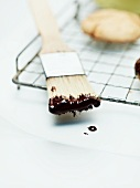 Cooking chocolate on a kitchen brush for decorating gingerbread biscuits