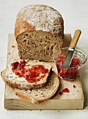 Organic country bread on a chopping board with strawberry jam