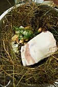 Pork Shoulder in Large Stock Pot with Aromatics of Garlic, and Rosemary; Laying on a bed of Hay