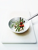 Green asparagus with cherry tomatoes and garlic in a pan