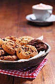 Chocolate chip cookies in a wooden bowl with a cappuccino in the background