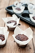 Chocolate muffins in parchment paper, some in a muffin tray