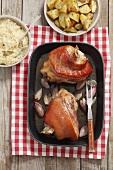 Pork knuckle with shallots, roast potatoes and sauerkraut