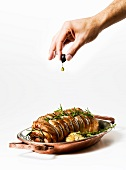 A hand squeezing olive oil out of an olive onto a veal roulade