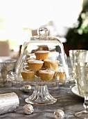 Mince pies under a glass cloches on a table laid for Christmas dinner