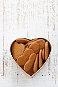 Heart-shaped gingerbread biscuits in a heart-shaped tin