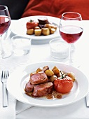 Fillet of lamb wrapped in ham with tomatoes and potatoes