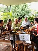 Menschen verschiedener Nationalitäten an einem Tisch mit malaysischen Spezialitäten