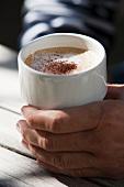 A hand holding a capuccino mug