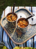 Beans with smoked bacon and maple syrup served in metal cups