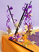Halloween decorations (black straws with purple ribbon and gold stars)