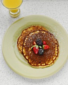 Organic Lemon Pancakes Topped with Berries and Powdered Sugar; Glass of Orange Juice