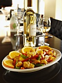 Orange Tempura Chicken with Red and Green Peppers, Pea Pods and Orange Slices; Bottle and Glass of White Wine