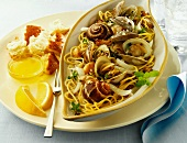 Clams and Escargot with Linguini in a Bowl; Bread and Lemon Slices