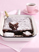 Brownies dusted with icing sugar in a baking dish