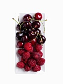 Fresh raspberries and cherries on a serving platter