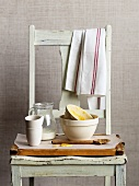 Dirty mixing bowls, a jug of milk and a wooden spoon on a wooden chair