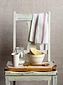 Schmutzige Rührschüsseln, Milchkrug und Kochlöffel auf Holzstuhl