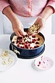 Raspberry cake with vanilla cream and slivered almonds being prepared