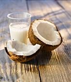 Aufgeschlagene Kokosnuss und ein Glas Kokosmilch