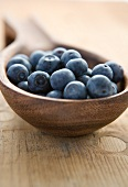 Fresh blueberries in a wooden ladle