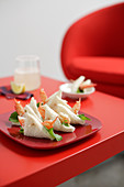 Prawn sandwiches on a red plate on a red table