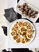 Meat balls with Parmesan and puff pastry spirals filled with anchovies and olives