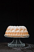A Madeira Bundt cake decorated with icing sugar on a cake stand