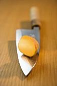 Half a potato on a knife