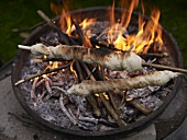 Stick bread being grilled on an open fire