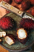 One Rambutan Peeled with Two Whole Rambutans; Knife