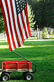 Red Wagon in a Yard with the American Flag; White Picket Fence in the Background