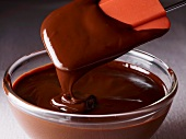 Chocolate sauce in a glass bowl with a spatula