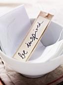 Kärtchen mit 'be inspired' Aufschrift in einem Schälchen