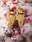 Two lady-shaped biscuits on a bed of flowers