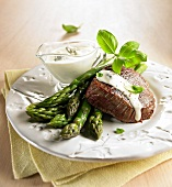 Beef steak with green asparagus and a blue cheese sauce