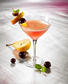 A fruit martini in a glass with fruit kebabs