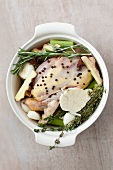 Raw chicken with herbs, spices and vegetables in a pot