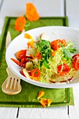 Frisee salad with peppers, marigold and peaches