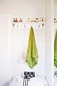 White wall shelf with hooks and hand towels hanging from them in the corner of a bathroom