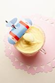 Vanillepudding, Löffel mit Spielzeugflugzeug dekoriert